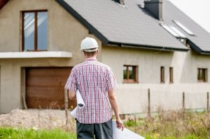 contractor with plans standing in front of house