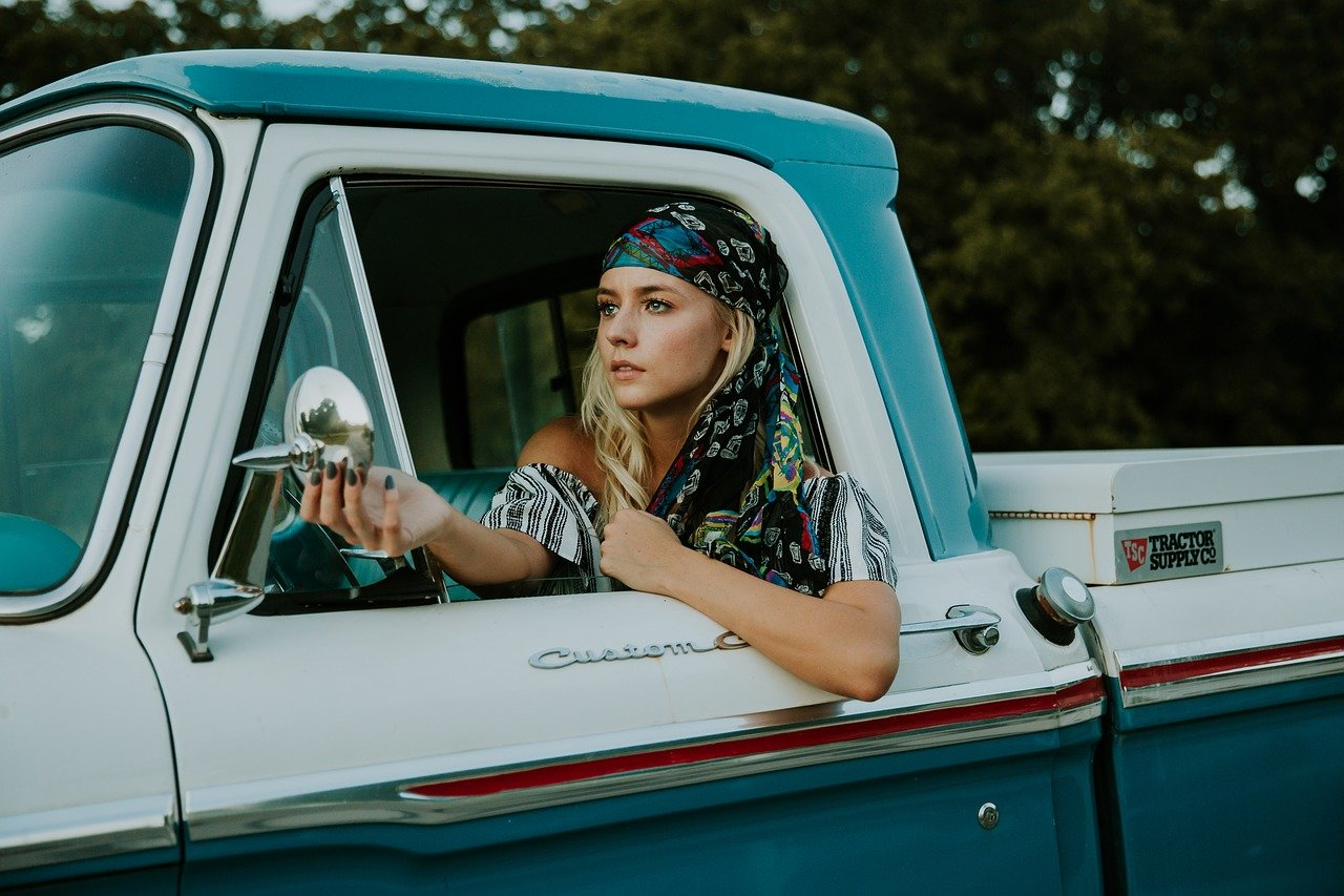Young female Driver at the wheel of a classic pickup truck